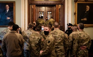 Members of the Pennsylvania National Guard look in on Senate proceedings at the Capitol in Washington on Friday, Jan. 22, 2021. Photos of Guard soldiers resting on the concrete floor of a parking garage sparked swift condemnation and apologies from members of Congress. Erin Schaff/The New York Times