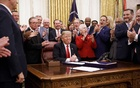 President Donald Trump signs the First Step Act and the Juvenile Justice Reform Act in the Oval Office of the White House in Washington, Dec 21, 2018. Trump doled out pardons to political allies and friends. But mixed in as well were cases that helped people serving overly harsh sentences. (Tom Brenner/ For The New York Times)
