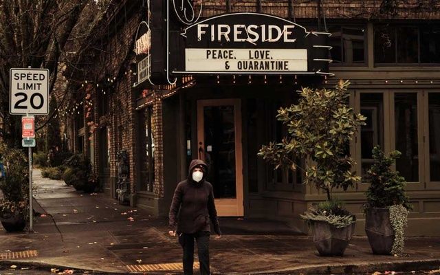 A pedestrian wearing a face mask walks through Portland, Ore, on Wednesday, Nov 18, 2020, the first day of a 14-day period of restrictions aimed at curtailing the spread of coronavirus. The New York Times