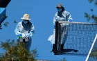People wearing personal protective equipment are seen disinfecting a tennis court after a training session as players undergo mandatory quarantine in advance of the Australian Open in Melbourne, Australia, Jan 22, 2021. REUTERS