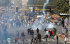 Police officers use tear gas during a protest against farm laws introduced by the government, in New Delhi, India, January 26, 2021. REUTERS