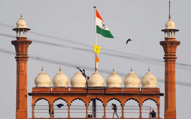 A man holds a flag as he stands on the top of the historic Red Fort during a protest against farm laws introduced by the government, in Delhi, India, January 26, 2021. REUTERS/Adnan Abidi