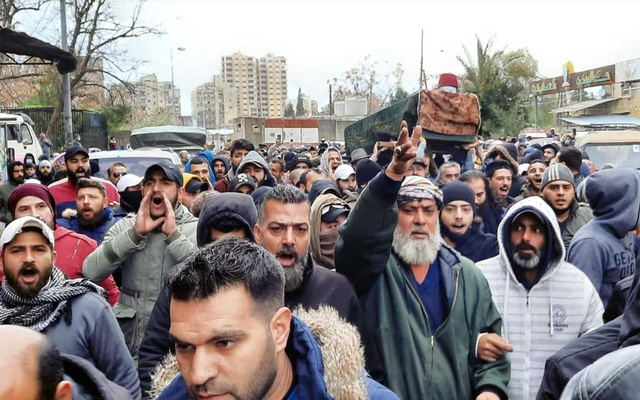 Men gesture and shout slogans as they carry the coffin of a protestor, who was killed in clashes between security forces and demonstrators during a protest against the lockdown and worsening economic conditions, during his funeral in Tripoli, amid the spread of the coronavirus disease (COVID-19), Lebanon Jan 28, 2021. REUTERS