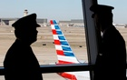 Pilots talk as they look at the tail of an American Airlines aircraft at Dallas-Fort Worth International Airport February 14, 2013. REUTERS