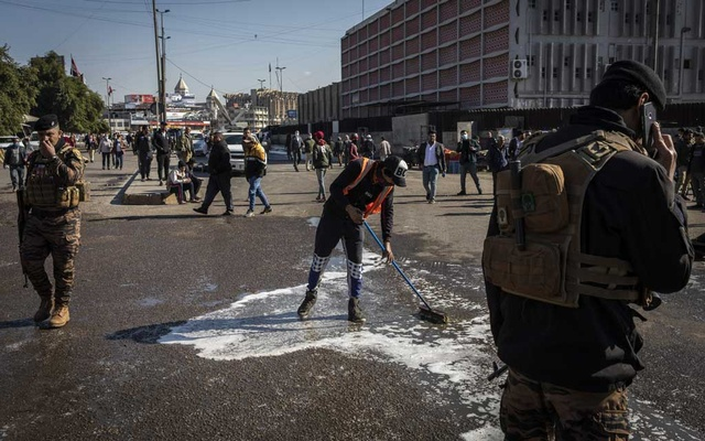 Workers clean a bloody street near Tayaran Square in Baghdad after twin suicide bombings left at least 32 dead, Jan 21, 2021.The New York Times