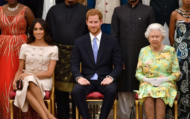 Britain's Queen Elizabeth, Prince Harry and Meghan, the Duchess of Sussex pose for a picture with some of Queen's Young Leaders at a Buckingham Palace reception following the final Queen's Young Leaders Awards Ceremony, in London, Britain Jun 26, 2018. Reuters