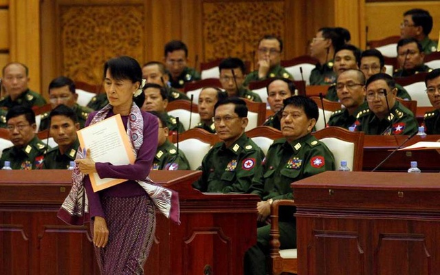 FILE PHOTO: Pro-democracy leader Aung San Suu Kyi walks to take an oath at the lower house of parliament in Naypyitaw May 2, 2012. REUTERS