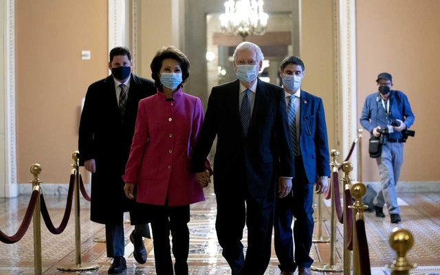 Senate Majority Leader Mitch McConnell walks with his wife, Secretary of Transportation Elaine Chao, at the Capitol in Washington Jan 3, 2021. The New York Times