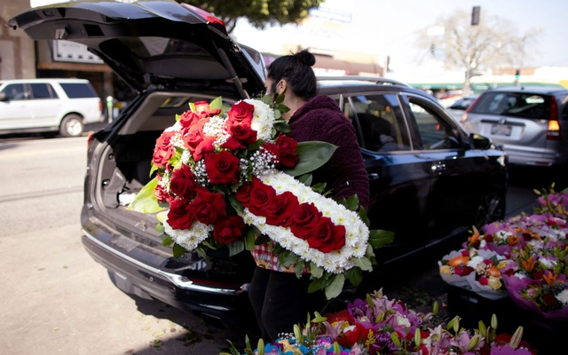 A woman lifts a funeral display into a car in the flower district as the coronavirus disease (COVID-19) outbreak continues, ahead of Valentine's Day in Los Angeles, California, US, Feb 4, 2021. REUTERS