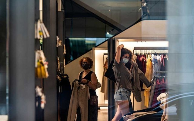 A shopper wearing a protective mask tries on clothes at a retail store following the outbreak of the coronavirus disease (COVID-19), in New York City, New York, US, July 5, 2020. REUTERS