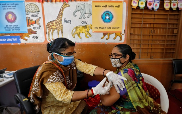 A health care worker receives a dose of COVISHIELD, a COVID-19 vaccine manufactured by Serum Institute of India, inside a classroom of school, which has been converted into a temporary vaccination centre, in Ahmedabad, India, February 9, 2021. Reuters