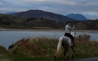 A woman rides her pony in the district of Connemara, amid the coronavirus disease (COVID-19) pandemic, in Claddaghduff, Ireland, February 6, 2021. REUTERS