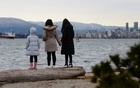 Maria Law, who emigrated from Hong Kong with her family, views the skyline with her daughters from Jericho Beach in Vancouver, British Columbia, Canada Jan 26, 2021. REUTERS