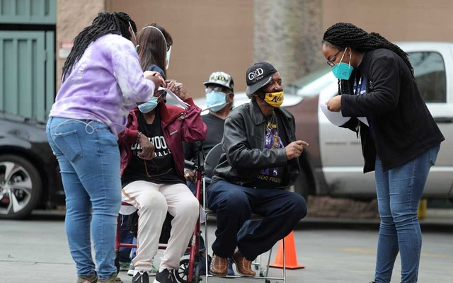 People sit as they wait to receive a coronavirus disease (COVID-19) vaccination at the LA Mission homeless shelter on Skid Row, in Los Angeles, California, US, Feb 10, 2021. REUTERS