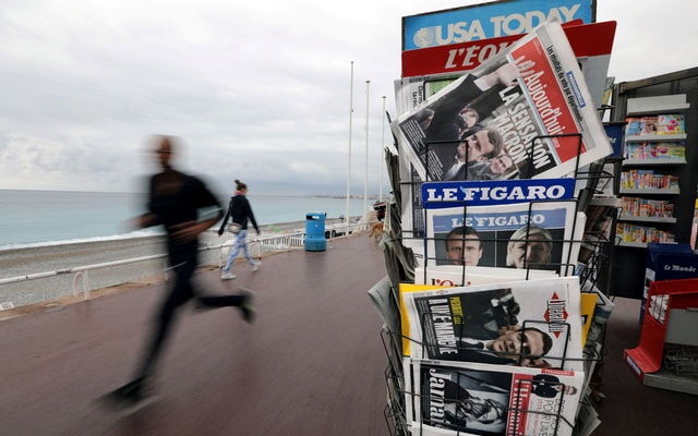 A man jogs past a news rack which displayed copies of French newspapers with front pages about the results in France's Presidential election on the Promenade Des Anglais in Nice, France, April 24, 2017. Reuters
