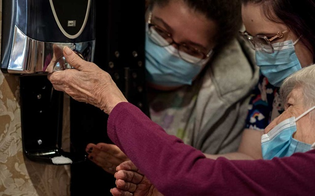 Staff members help a resident of the Good Shepherd Nursing Home sanitise their hands in Wheeling, W Va, on Monday, Feb 8, 2021. Amr Alfiky/The New York Times