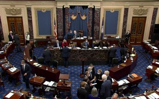 US Senate Minority Leader Mitch McConnell (R-KY) huddles on the Senate floor with Senator Kyrsten Sinema (D-AZ), Senator John Barrasso (R-WY), Senator John Hoeven (R-ND), Senator Dan Sullivan (R-AK), Senator James Lankford (R-OK), Senator Joni Ernst (R-IA) and Senator John Cornyn (R-TX) and others after the Senate voted for witnesses during the fifth day of the impeachment trial of former president Donald Trump on charges of inciting the deadly attack on the US Capitol, on Capitol Hill in Washington, US, February 13, 2021. US Senate TV/Handout via Reuters