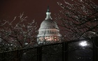 The US Capitol is seen through ice-covered tree branches above barbed wire on a security fence after the Senate voted to acquit former US President Donald Trump during his impeachment trial, in Washington, US February 13, 2021. REUTERS