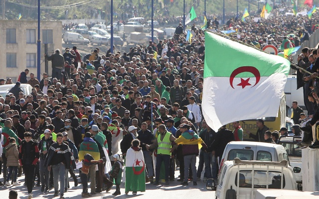 Demonstrators carry national flags as they gather in the town of Kherrata, marking two years since the start of a mass protest movement there demanding political change, Algeria February 16, 2021. REUTERS