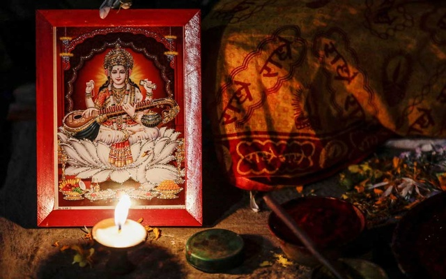 A butter lamp is offered near the portrait of the Goddess Saraswati during the Shreepanchami festival, dedicated to goddess of education Saraswati in the belief that the goddess will help devotees excel in education, in Kathmandu, Nepal Feb 16, 2021. REUTERS
