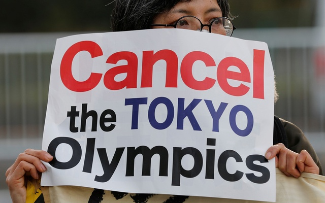 A woman holds a banner during a rally in front of a building housing the Organising Committee of the 2020 Tokyo Olympic Games to demand the Games' cancellation and to criticise comments made by Tokyo 2020 Olympics chief Yoshiro Mori in Tokyo, Japan, Feb 12, 2021. REUTERS