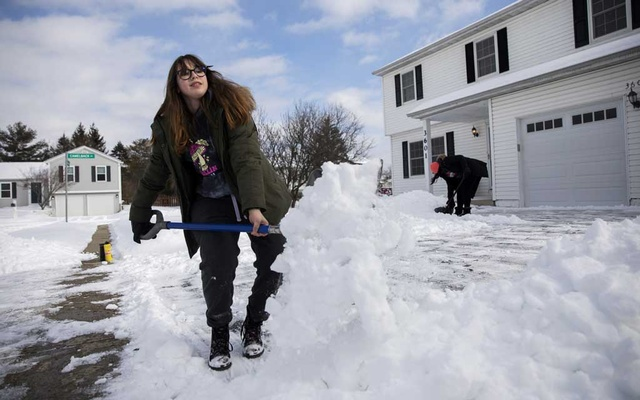 Lynden Davidson, 16, and Tempa Cole, 14, shovel driveways in their neighbourhood for $20 a drive in Columbus, Ohio, Feb 16, 2021. Power grids are designed to handle spikes in demand, but the wild and unpredictable weather linked to global warming will very likely push grids beyond their limits. (Maddie McGarvey/The New York Times)