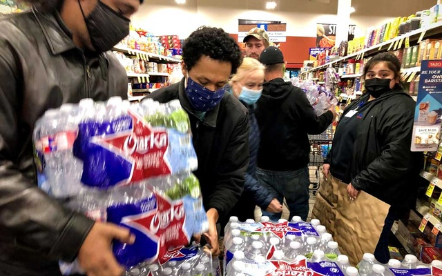 Shoppers crowd a display of bottled water at a United Supermarkets location not long after the city announced it had 2-3 hours of water left at normal consumption, due to loss of electric power caused by the winter storm in Abilene, Texas, US February 15, 2021.