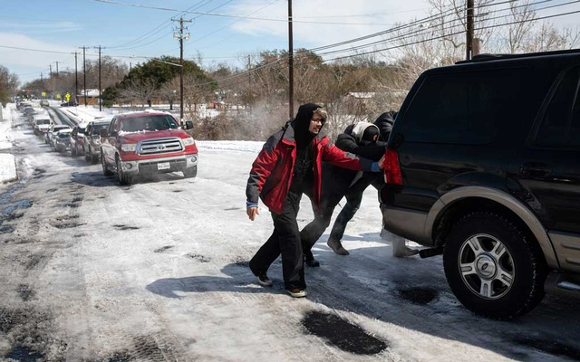 People help a motorist up a snow and ice-covered road on Tuesday, Feb 16, 2021, in Austin, Texas. The New York Times