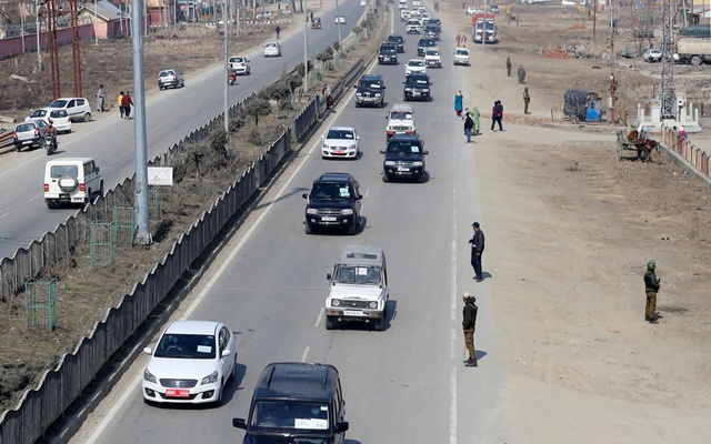 Indian policemen stand guard as a convoy carrying foreign diplomats moves on a road in Srinagar, Feb 17, 2021. REUTERS