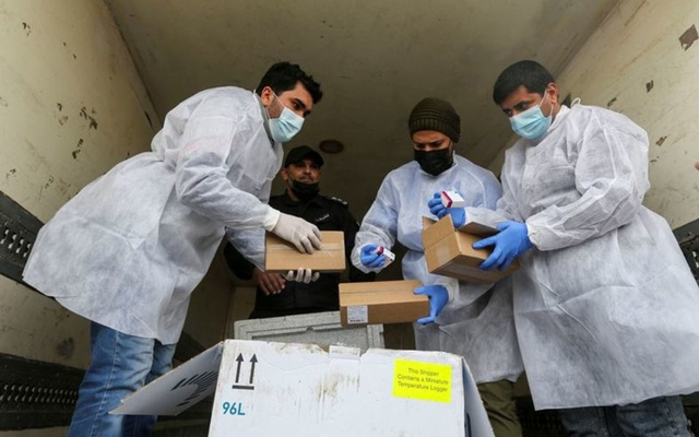 Palestinian workers unload the first shipment of coronavirus disease (COVID-19) vaccines, in the Southern Gaza Strip February 17, 2021, REUTERS.