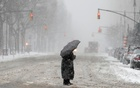 A woman stands in a crosswalk in heavy falling snow on Central Park West during a winter storm on the upper west side of Manhattan in New York City, New York, US, February 1, 2021. Reuters