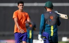 Arjun Tendulkar, son of Sachin Tendulkar, speaks with Australia's Aaron Finch during training. Reuters