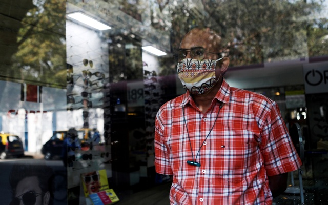 Narendra Gada waits for customers inside his brother's spectacle shop in Mumbai, India, Jan 19, 2021. REUTERS
