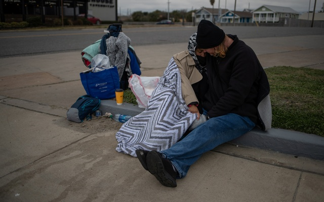 Couple Renne Alva, 37, and Travis Wasicek, 43, sit amongst their belongings along Seawall Boulevard as they embrace to keep each other warm after record-breaking winter temperatures in Galveston, Texas, US, February 18, 2021. The couple said they became homeless last year after losing their jobs due to the economic fallout from the coronavirus (COVID-19) global pandemic. REUTERS