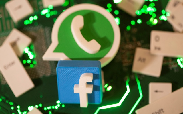 3D printed Facebook and WhatsApp logos and keyboard buttons are placed on a computer motherboard in this illustration taken Jan 21, 2021. REUTERS