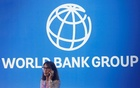 A participant stands near a logo of World Bank at the International Monetary Fund - World Bank Annual Meeting 2018 in Nusa Dua, Bali, Indonesia, October 12, 2018. Reuters