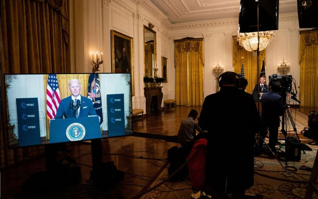 President Joe Biden, is shown on a video monitor as he delivers remarks, right, from the White House in Washington during a videoconference hosted by the Munich Security Conference on Friday, Feb. 19, 2021. (Anna Moneymaker/The New York Times)