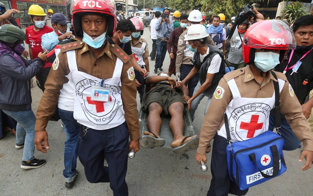 Rescue workers carry an injured man after protests against the military coup, in Mandalay, Myanmar, February 20, 2021. Reuters