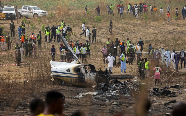People and rescuers gather at the site where a Nigerian air force plane crashed while approaching the Abuja airport runway, according to the aviation minister, in Abuja, Nigeria February 21, 2021. REUTERS/Afolabi Sotunde