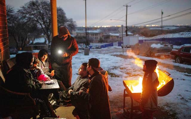 The Traugott family, with no power in their apartment, play a game of Uno outside while warming up by burning wood fire scavenged from a discarded armoire, in Austin, Texas, Feb 17, 2021. Part of the responsibility for the near-collapse of the Texas electrical grid during the snowstorm can be traced to the decision in 1999 to embark on the nation's most extensive experiment in electrical deregulation. (Tamir Kalifa/The New York Times)