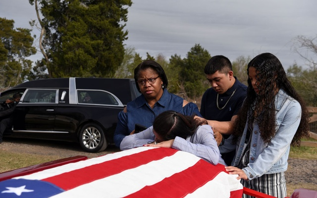Lila Blanks is comforted by her friend Nikki Wyatt, her son Brandon Danas, 17, and her daughter Bryanna Danas, 14, as she reacts by the casket of her husband, Gregory Blanks, 50, who died from complications from the coronavirus disease (COVID-19), ahead of his funeral in San Felipe, Texas, US, January 26, 2021. Reuters