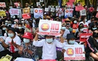 Demonstrators hold placards during a rally against the military coup in front of Indonesian embassy in Yangon, Myanmar, February 24, 2021. REUTERS