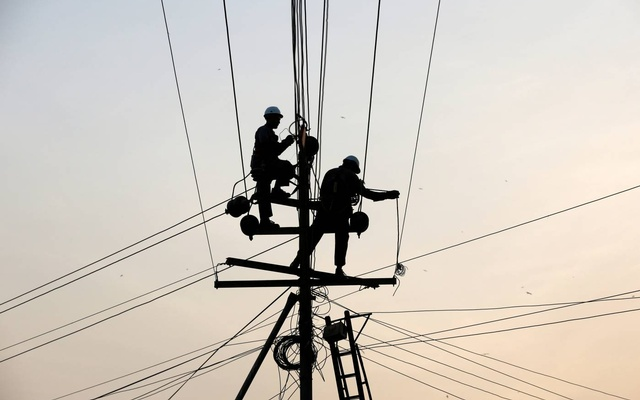 Technicians are silhouetted as they fix cables on a power transmission line in Karachi, Pakistan, January 9, 2017. REUTERS/Akhtar Soomro