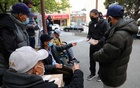 Max Leung, second from right, hands out information on how to report a hate crime to a group of men playing cards in San Francisco's Chinatown neighbourhood on Thursday, Dec. 11, 2021. Attacks on Asian-American seniors have renewed fears over a wave of anti-Asian violence and harassment that was spurred earlier in the pandemic. (Jim Wilson/The New York Times)