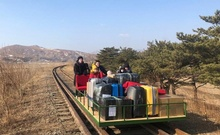 Russian diplomats and family members use a hand-pushed rail trolley to leave North Korea amid the coronavirus disease (COVID-19) restrictions while crossing the demarcation line between North Korea and Russia, February 25, 2021. Russian Foreign Ministry/Handout via REUTERS