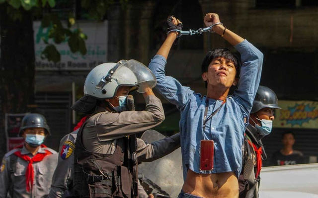 A pro-democracy protester is detained by riot police officers during a rally against the military coup in Yangon, Myanmar, February 27, 2021. REUTERS