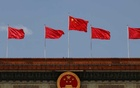 A Chinese flag flutters above the Chinese national emblem at the Great Hall of the People after the opening session of the National People's Congress (NPC) in Beijing, China May 22, 2020. REUTERS