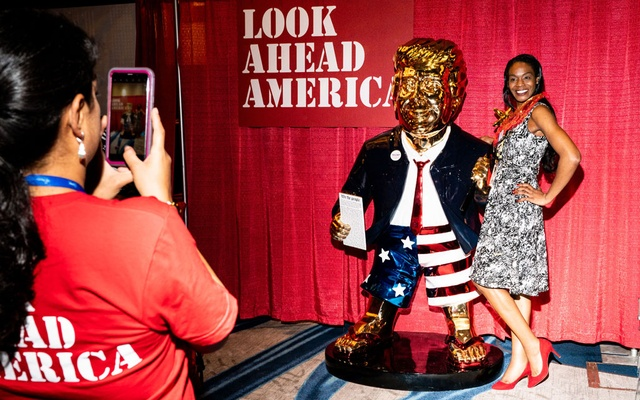 A woman poses for a photo next to a metal replica of former President Donald Trump, made by Tommy Zegan, at the Conservative Political Action Conference (CPAC) in Orlando, Fla., on Friday, Feb. 26, 2021. The faithful who flocked to the annual conference of conservatives made it clear that their allegiance was to the former president far more than to the Republican Party. (Erin Schaff/The New York Times)