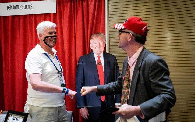 Timothy Shea and Johnny Flynn, a Republican who is running for Senate in Connecticut, fist bumps in front of a cardboard cutout of former President Donald Trump, at the Conservative Political Action Conference (CPAC) in Orlando, Fla., on Friday, Feb. 26, 2021. The faithful who flocked to the annual conference of conservatives made it clear that their allegiance was to the former president far more than to the Republican Party. (Erin Schaff/The New York Times)