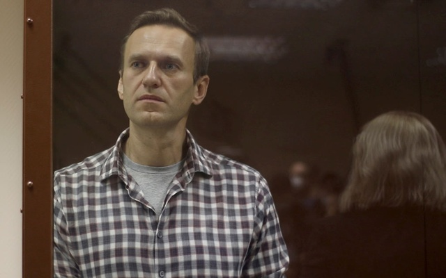 Kremlin critic Alexei Navalny stands inside a defendant dock during a court hearing in Moscow, Russia, Russia February 20, 2021, in this still image taken from video. Press Service of Babushkinsky District Court of Moscow/Handout via REUTERS